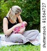 Portrait of happy mother and mixed race newborn baby girl outdoors at park - stock photo