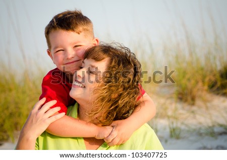 Portrait of happy mother and son hugging at beach with sand dunes in background - stock photo