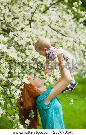 Portrait of happy mother and son in spring garden. They playing and laughing. Blooming apple-trees. Family concept.  - stock photo
