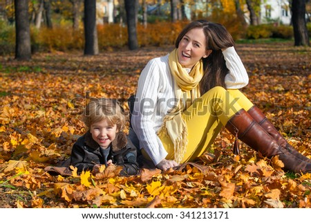 Portrait of happy mother and son relaxing in the park and enjoying in autumn season. - stock photo