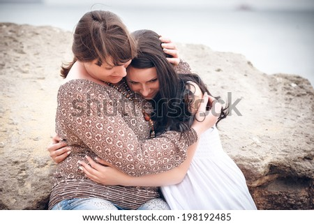 portrait of happy mother and the daughter on the seashore - stock photo