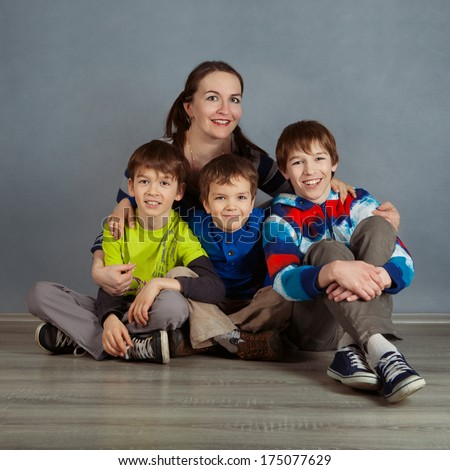 Portrait of happy mother and three sons on gray background - stock photo