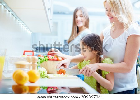 Portrait of happy mother and two daughters cooking in the kitchen - stock photo