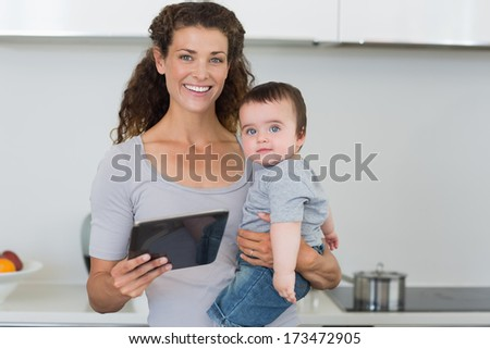 Portrait of happy mother carrying baby boy while holding digital tablet in kitchen at home - stock photo
