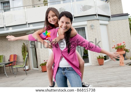 Portrait of happy mother carrying her daughter on back outside their home - stock photo