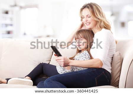 Portrait of happy mother embracing her cute daughter while watching tv at home. Happy family relaxing on the coach.  - stock photo