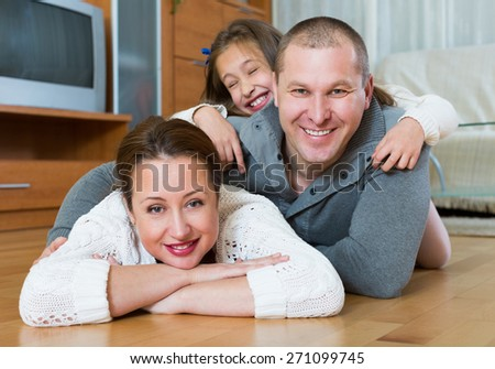 Portrait of happy mother, father and cute girl together indoors - stock photo