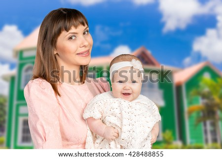 Portrait of happy mother holding her baby daughter - stock photo