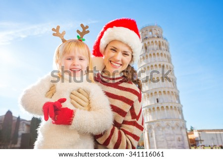 Portrait of happy mother in Christmas hat and daughter wearing funny reindeer antlers standing in front of Leaning Tour of Pisa, Italy. They spending exciting Christmas time traveling. - stock photo
