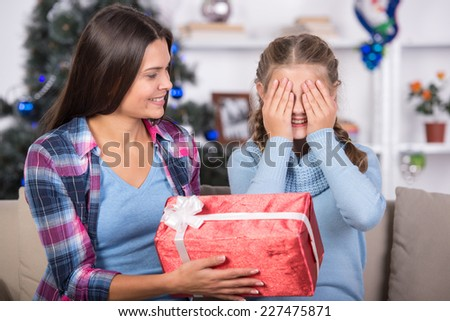 Portrait of happy mother is giving a gift to her daughter.  It's Christmas time. - stock photo