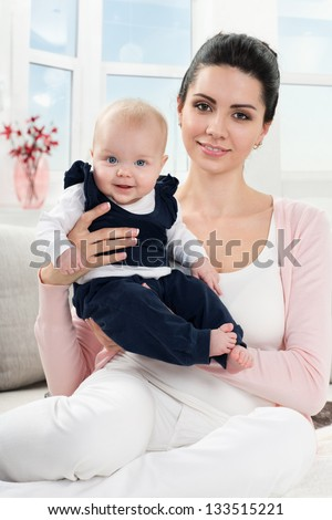 portrait of happy mother with a baby at home - stock photo