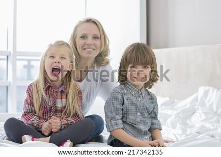 Portrait of happy mother with children in bedroom - stock photo