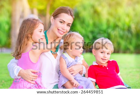 Portrait of happy mother with cute little babies sitting on fresh green grass field, having fun outdoors, enjoying parenthood, happiness and love concept - stock photo
