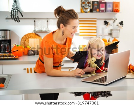Portrait of happy mother with daughter in halloween bat costume having video chat on laptop with friends in decorated kitchen. Traditional autumn holiday - stock photo