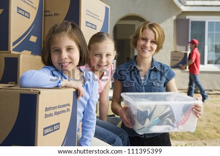 Portrait of happy mother with daughters moving into new house - stock photo