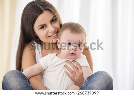 Portrait of happy mother with her little baby in her room.