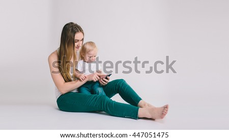 Portrait of happy mother with her little baby isolated on white background. Children's educational games on mobile phones - stock photo