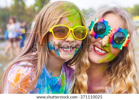 Portrait of happy mother with little daughter on holi color festival - stock photo