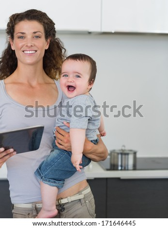 Portrait of happy mother with tablet computer carrying cheerful baby boy in kitchen at home - stock photo