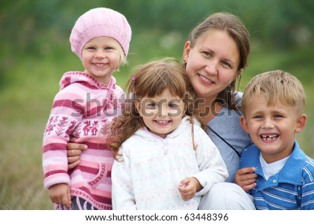 Portrait of happy mother with three children outdoors - stock photo