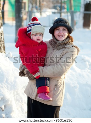 Portrait of happy mother with toddler  in winter - stock photo