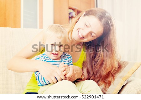 Portrait of happy mother with toddler on sofa in home interior. Focus on woman