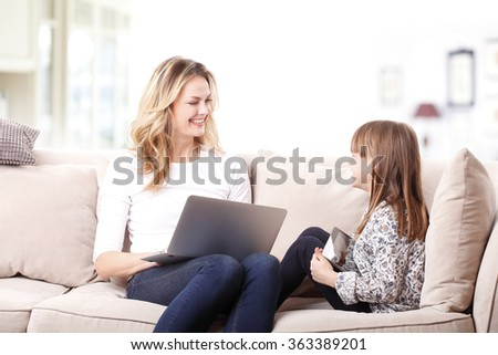 Portrait of happy mother working online with laptop while sitting at home with her cute daughter. Little girl holding in her hands a mobile phone.