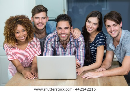 Portrait of happy multi-ethnic friends using laptop on table at home - stock photo