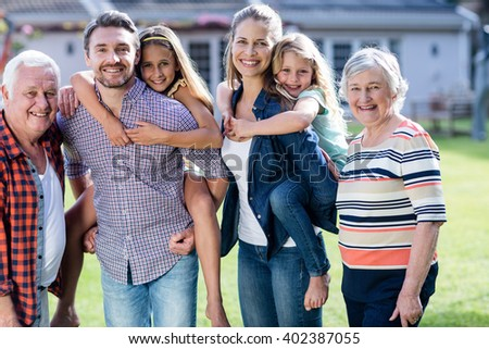 Portrait of happy multi-generation family standing together in the garden - stock photo