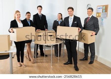 Portrait Of Happy Multiethnic Employees In Office Holding Cardboard Boxes - stock photo