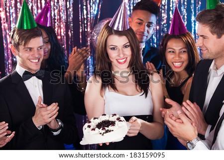 Portrait of happy multiethnic friends celebrating birthday at nightclub - stock photo