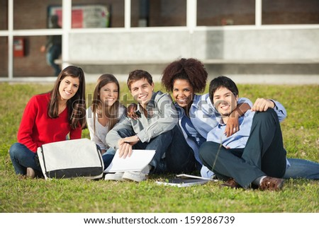Portrait of happy multiethnic students sitting on grass at college campus