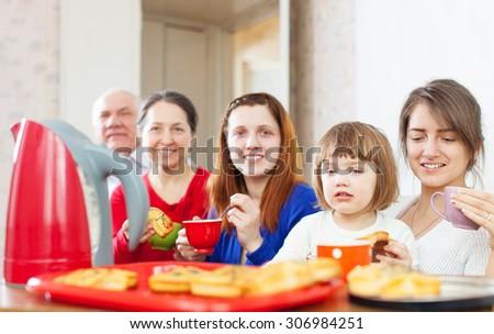 Portrait of happy multigeneration family communicate around tea table  - stock photo