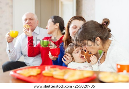 Portrait of happy multigeneration family communicate over tea with cakes at home interior