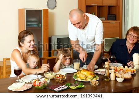 Portrait of happy multigeneration family  eating chicken with wine at home together - stock photo