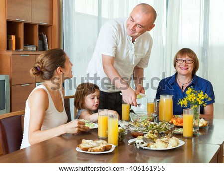 Portrait of happy multigeneration family  eating fish with juice at home together - stock photo