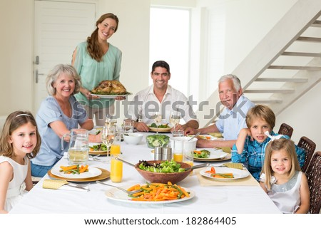 Portrait of happy multigeneration family having meal at dining table - stock photo