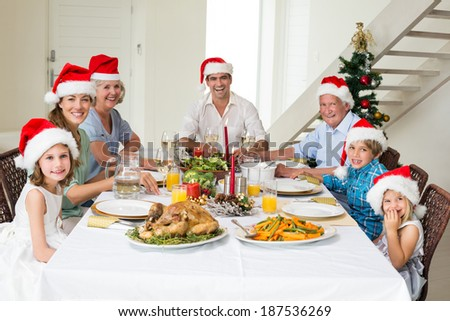 Portrait of happy multigeneration family in Santa hats having Christmas meal at dining table - stock photo
