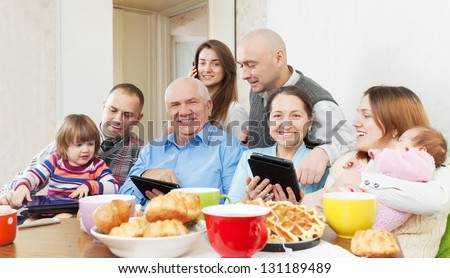 Portrait of happy multigeneration family uses electronic devices over tea - stock photo