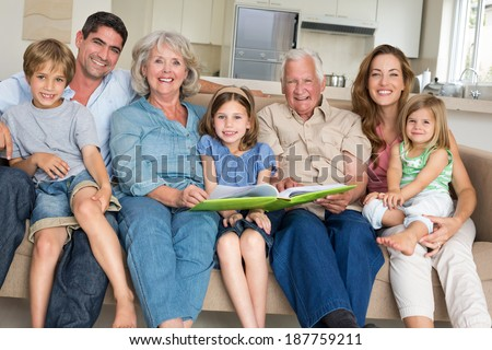 Portrait of happy multigeneration family with storybook at home - stock photo