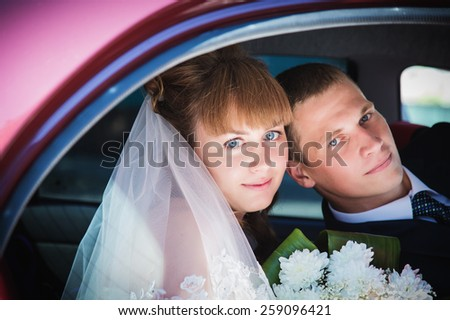 Portrait of happy newly wed couple in car - stock photo