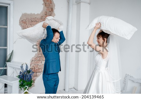 Portrait of happy newlywed couple fighting with pillows