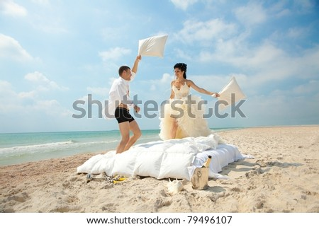 Portrait of happy newlywed couple fighting with pillows in bed on the beach - stock photo