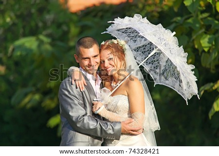 Portrait of happy newlyweds outdoors - stock photo