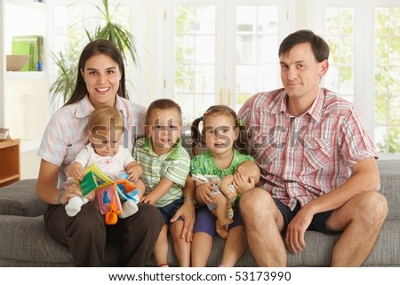 Portrait of happy nuclear family with 3 children sitting on sofa at home, looking at camera, smiling. - stock photo