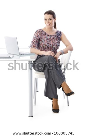Portrait of happy office assistant sitting at desk, laughing at camera, full length picture isolated on white.