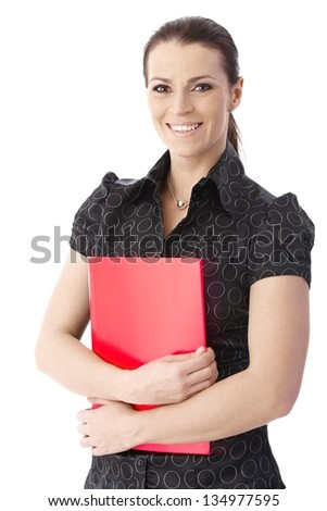 Portrait of happy office worker woman standing with red folder handheld, smiling at camera. - stock photo