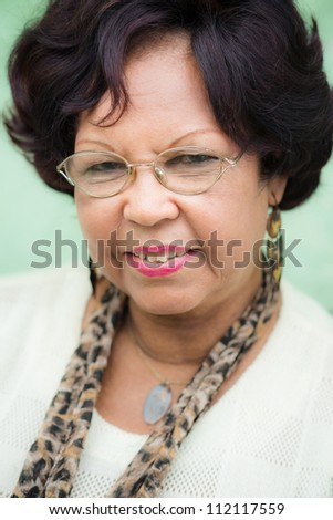 Portrait of happy old african american woman with glasses and wig smiling at camera - stock photo