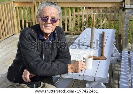 Portrait of happy old man in his 90's. sit in his home garden and hot drink. Concept photo of senior citizen, retirement, pensioner, health and aging.