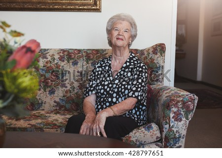 Portrait of happy old woman sitting on a sofa. Senior woman relaxing at old age home. - stock photo